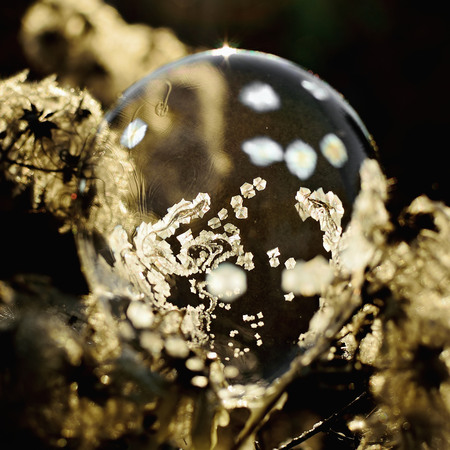 patter: Frozen soap bubble. Cold winter liquid ball experiment. Freezing water with icy patter texture