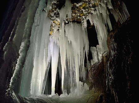 iluminated: Winter icicles iluminated with battery and candles. Frozen cave in Slovakia. Stalactite and stalagmite. Exploration depths of the earth.
