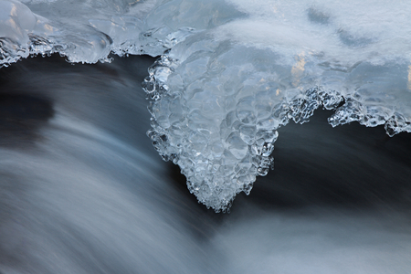 flux: Water and ice in winter mountain stream. Cold icing shapes. Stock Photo