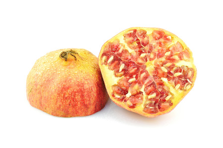 Pomegranate with seeds on white background. Half of exotic fruit. Natural antioxidant. Tasty organic product.