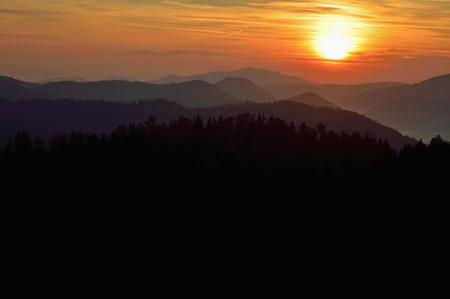 Sunrise in Slovakia. Orange sun dark sky over mountains. Romantic atmosphere. Fog hills at sunset.