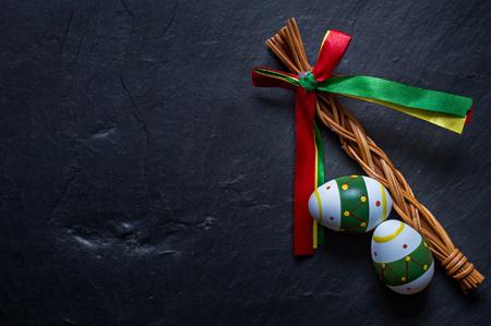 Huevos de Pascua coloreados y látigo en la mesa de piedra. Símbolo de unas vacaciones de religión cristiana. Fondo de tradición popular de primavera.