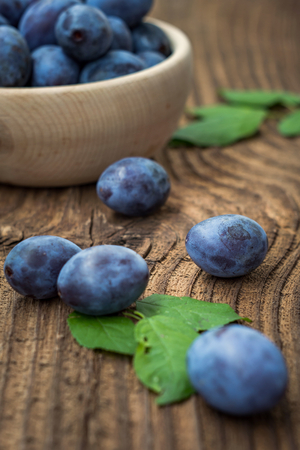Fresh blue plums on wood table background. Sweet autumn fruit. Delicious and healthy raw food full of vitamins. Stok Fotoğraf