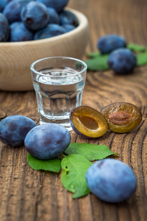 Fresh blue plums and plum brandy on wood table background. Sweet autumn fruit. Delicious and healthy raw food full of vitamins. Alcohol drink in glass dram.