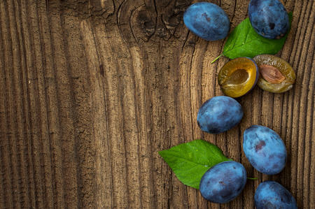 Fresh blue plums  on wood table background. Sweet autumn fruit. Delicious and healthy raw food full of vitamins.