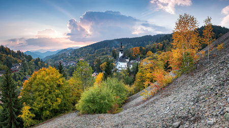 Fall in Slovakia. Old mining village. Historic church in Spania dolina. Autumn colored trees at sunset. Stok Fotoğraf