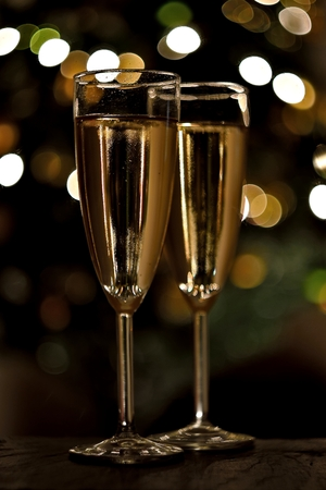 New year celebration with two champagne glasses on wooden table with bokeh background. Bubbly alcohol drink.