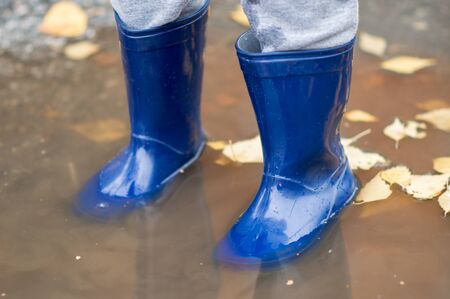 Feet of child in blue rubber boots jumping over a puddle after the rain. Close up of child wellies in autumn weather