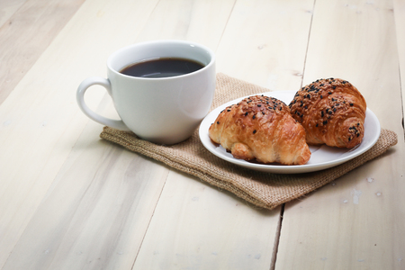 Croissant and coffee  isolated on wood table