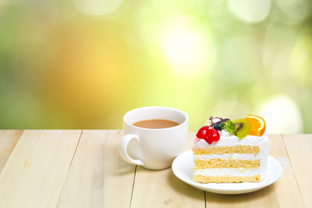 Slice cake with coffee cup on wood , green blur background Stock Photo