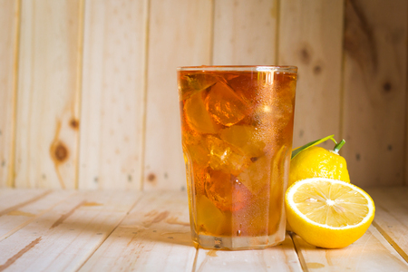 Glasses of ice tea with lemon slices  on wooden background