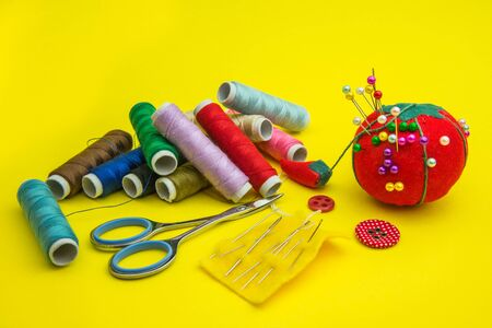 sewing tools and bobbins thread isolated on yellow background