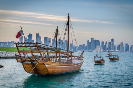 moored: Dhows moored off Museum Park in central Doha, Qatar, with some of the buildings from the citys in the background. Editorial