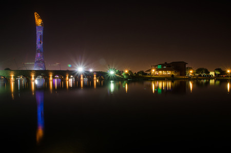 The Aspire Park and Aspire Tower or Torch Hotel in Doha Sports City at night Editorial