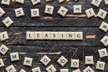 Leasing word made of square letter word on wooden background. Standard-Bild