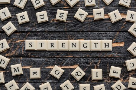 Strength word made of square letter word on wooden background. Standard-Bild