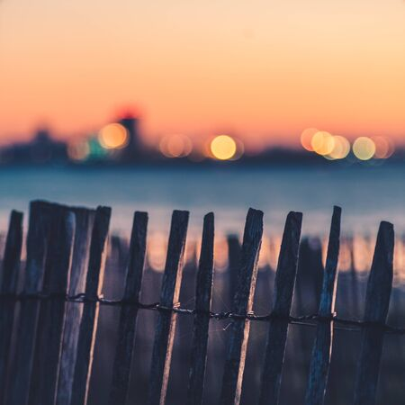 A close up of an old wooden fence near the sea at sunrise. Colorful City light In the blurred background. Sky is orange