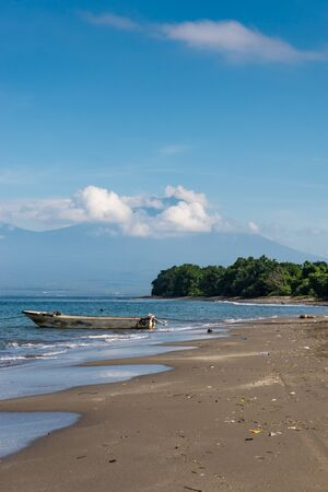 Balinese tropical beach with blue sky And palm trees. An old boat on the sand. Volcano with clouds in the foreground. Portrait format Zdjęcie Seryjne