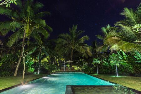 illuminated swimming pool at night in a tropical garden