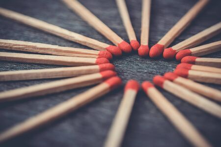 Matchstick with a red heart-shaped head on a wooden background. 스톡 콘텐츠