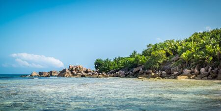 Panoramic view of nice tropical sandy beach with famous granite rocks on Anse Coco beach, La Digue Island, Seychelles. Holiday and vacation concept. Tropical beach on background blue sky Stock Photo