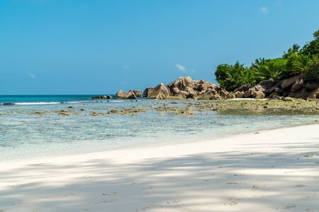 Beautiful beach. View of nice tropical sandy beach with famous granite rocks on Anse Coco beach, La Digue Island, Seychelles. Holiday and vacation concept. Tropical beach on background blue sky Stock Photo