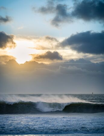 Sunrise over the sea during a storm. Dramatic clouds and rays of the sun illuminate ocean spray .