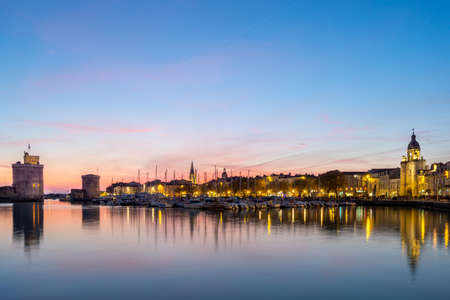 Panoramic view of the old harbor of La Rochelle at sunset with its famous old towers. beautiful pastel color sky