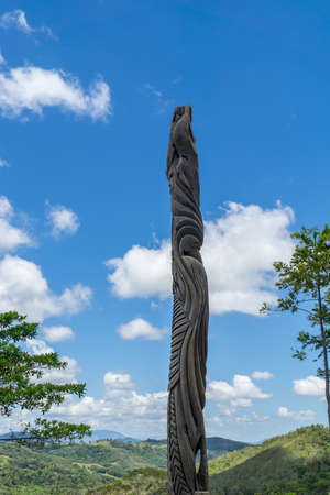 Huge typical new caledonian wooden totem. Grandes Fougères Park, New Caledonia. Sky is blue