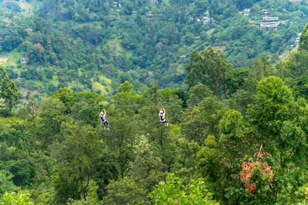 Men going on a zipline in the jungle. tree climbing in Sri Lanka. adventure, challenge and sport concept Stock Photo