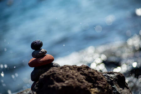 Closeup shot of pebbles stacked on each other in a balance with the blue sea in the background Stock fotó