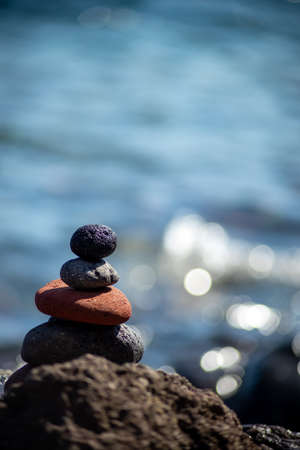 Close-up shot of pebbles stacked on each other in a balance with the blue sea in the background