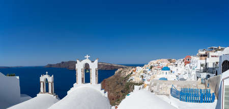 Panoramic view of Santorini caldera with Oia town and famous old white tower bells and blue domes of orthodox churches