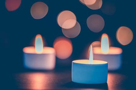 Three burning candles in front of a beautiful colorful circle shiny bokeh background