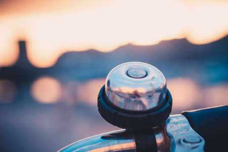 close-up of a bell ringer on the handle bars of bicycle in the old harbor of La Rochelle at sunset. beautiful bright and blurred background