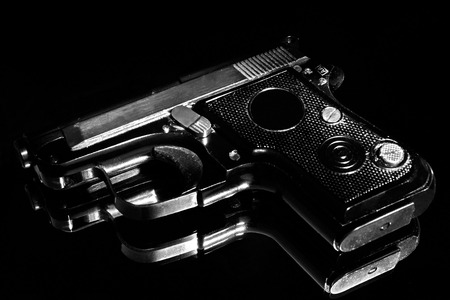 Handgun on the glass surface, Close-up.