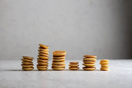 Mini-pancakes are stacked on the table in stacks of different heights. Small pancakes look like coins.