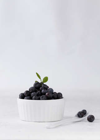 Blueberries with a green leaf in a white cup on a white table, next to a spoon
