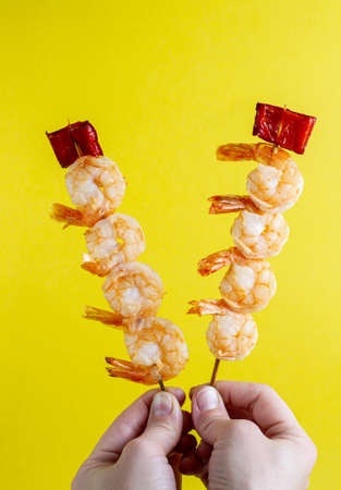 Shrimp kebabs with bell pepper on skewers in hands on a yellow background stick out in different directions