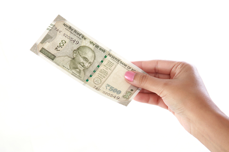Hand holding 500 rupee notes against white background