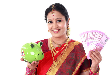 Traditional Indian woman holding piggy bank and Indian currency Stock Photo