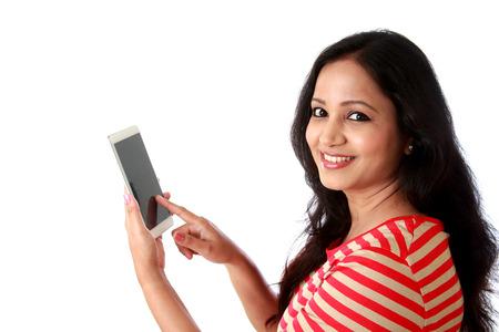 Mujer joven sonriente que manda un SMS contra blanco