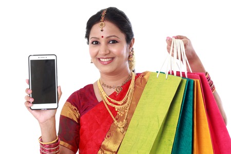 Happy traditional woman with shopping bags and mobile phone Stock Photo