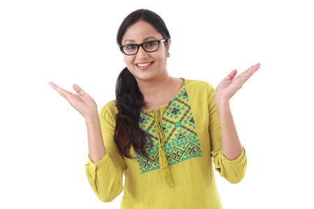 Excited young indian woman against white background Stock Photo