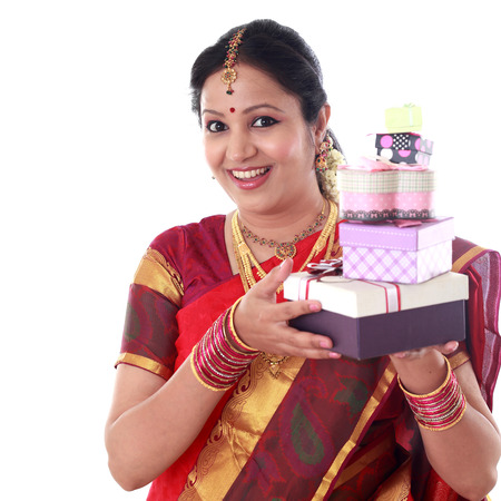 Traditional Indian woman holding gift boxes against white background