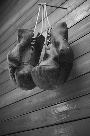 Old boxing gloves hang on nail on wooden wall with copy space for text. High resolution 3d render Banco de Imagens