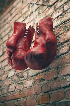 Old red boxing gloves hang on nail on brick wall with copy space for text. High resolution 3d render Stockfoto