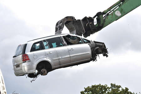 Car in a scrap yard being lifted by a mechanical grabber crane to be scrapped