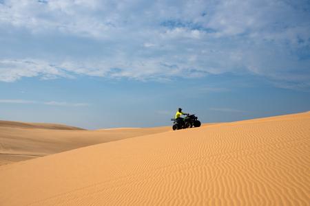 ATV racing drive on sand dune.