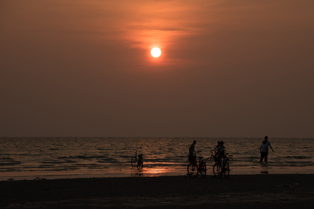 silhouette people playing on beach in the sea on sunset background Stock Photo